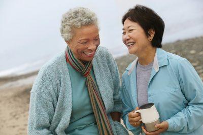 Two-female-friends-talking-on-beach