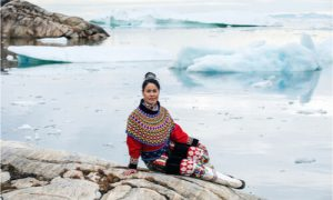 The Inuit lady sits on the dried rock.